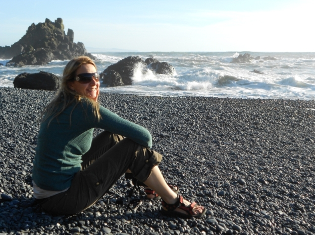 Woman sitting on cobble beach