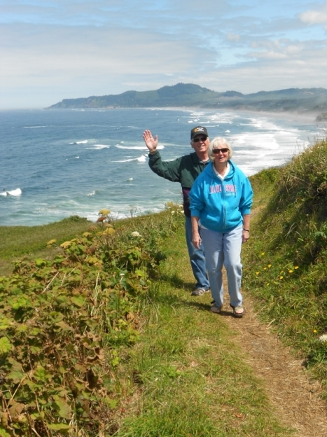 Couple hiking up hill with ocean in background