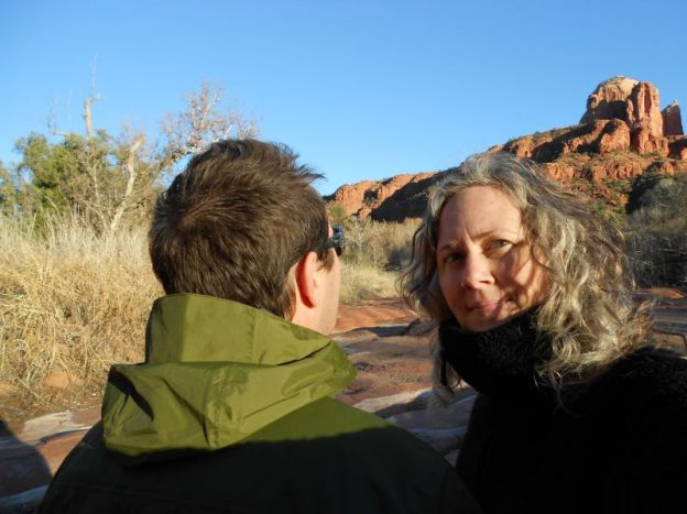 Back of man's head and woman's face with red rock in background