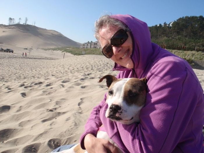 Woman hugging dog on beach