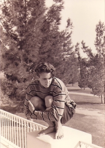 young man squatting on wall with pine trees in background