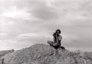 young man sitting atop rock looking through video camera