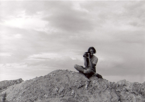 young man sitting atop rock looking through video camera