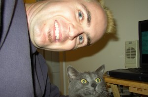Photo of blonde man and gray cat