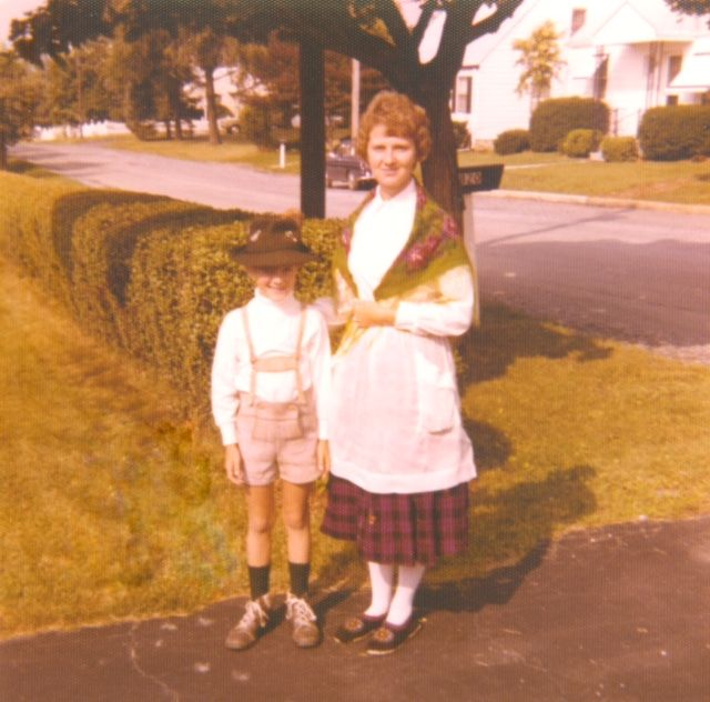 Photo of a white child and white adult woman dressed in traditional German clothing with green grass, a hedge and road in the background